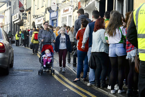 A mother and her children negotiate traffic and students during this week's unofficial Rag Week in the city.